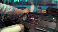 Bus driver sits behind the steering wheel of intercity coach at night station Stock Footage