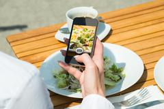 Close-up Of Person's Hand With Mobile Phone Taking Picture Of Food At Restaur Stock Photos