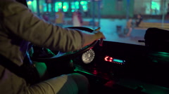 Driver behind the wheel of intercity coach leaves bus station terminal at night Stock Footage