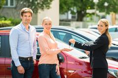 Side View Of Female Dealer Giving Car Key To Happy Couple Stock Photos