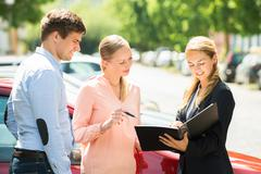 Saleswoman Explaining Contract Paper To Happy Couple Buying A New Car - stock photo