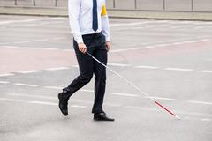 Blind Person With White Stick Walking On Street - stock photo