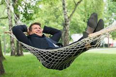 Happy Young Businessman Lying In Hammock At Park Stock Photos