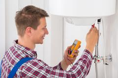 Smiling Male Plumber Examining Electric Boiler With Multimeter Probe Stock Photos