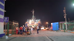 Group of people with their luggage boarding the ferry in Port Kavkaz at night Stock Footage
