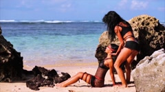Sexy slow motion of two beautiful young women on a sunny tropical beach. Stock Footage