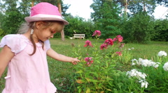 Little girl takes care of the flowers in the park. She loved flowers Stock Footage