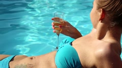 Couple has a rest in the pool with champagne. they are smiling, hugging and Stock Footage