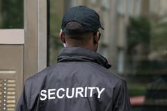 Rear View Of A Male Security Guard Wearing Black Uniform - stock photo