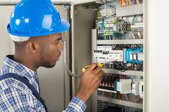 Close-up Of Young Male Technician Examining Fusebox With Screwdriver Stock Photos