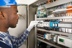 Photo Of Young African Male Technician Checking Fusebox Stock Photos