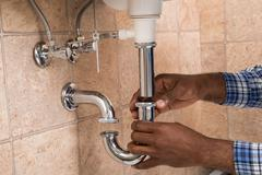 Close-up Of Male Plumber's Hand Fixing Sink In Bathroom Stock Photos