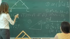 Female teacher at high school washes the chalkboard and lookng to the people in - stock footage
