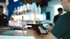 Caucasian man places his card to pay the bill on the bar counter Stock Footage