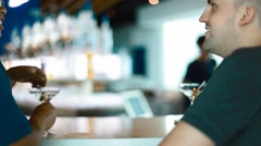 Two men converse over drinks at the bar counter Stock Footage
