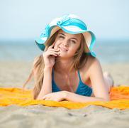 Young lady sunbathing on a beach. Beautiful woman posing at the Kuvituskuvat