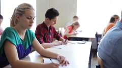 Students with notebooks writing test at school Stock Footage