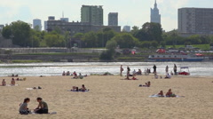 Group of teenagers on an urban beach, skyline background - River in Warsaw Stock Footage