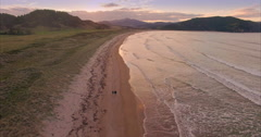 Aerial of couple walking on tropical beach at Waikawau Bay, New Zealand Stock Footage