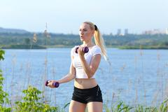 Athlete female weighted arm legs workout outdors - stock photo