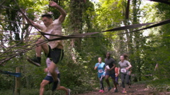 4K Competitors in endurance sport event struggling over cargo net but having fun Stock Footage