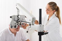 Happy Female Optometrist Doing Sight Testing For Patient In Clinic - stock photo