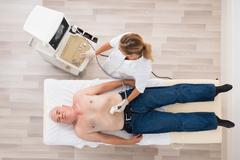 High Angle View Of A Young Female Doctor Using Ultrasound On Abdomen Of Senio Stock Photos