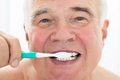Senior Man Brushing His Teeth With Toothbrush Stock Photos
