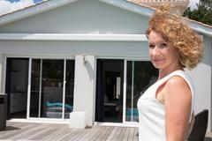 Woman real estate agent in front of a house for sale Stock Photos