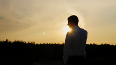 Silhouette of a young businessman talking on the phone. It stands on a sunset Stock Footage
