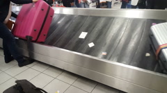 Tourists pack their luggage from the baggage claim at the airport Stock Footage