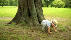 Sweet baby playing peek-a-boo with mother near tree Stock Footage