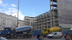 2 concrete mixer trucks on construction site in city street - sunny summer day Stock Footage