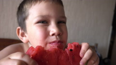 Happy boy eating delicious red watermelon and juices flowing on her cheeks - stock footage