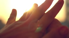 Groom slipping ring on finger of bride on sunset city background in slowmotion Stock Footage