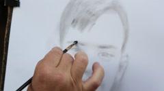 Street artist paints a portrait of a boy Stock Footage