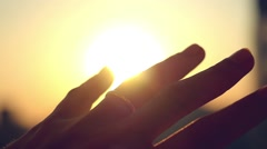 Hand with ring on finger of bride touch the sun on sunset city background in Stock Footage