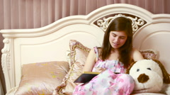 Young woman writing diary while sitting on the bed Stock Footage