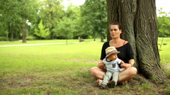 Mother is meditating at the park with little son  Stock Footage