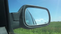 Driving through countryside, view in car side mirror Stock Footage