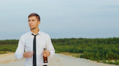 Young businessman with a bottle of alcohol is on the sand, weakens tie. Concept Stock Footage