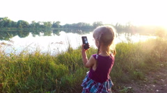 Little girl is working on the smartphone. Her fingers touch the touch screen. Stock Footage