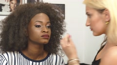 Makeup artist applying eye lashes on black african american model. Beauty salon - stock footage