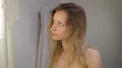 young girl after shower drying long blond hair in bathroom of hotel - stock footage