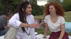 Boy with rasta dreadlocks and redhead girl flirting during picnic in park Stock Footage