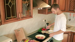 Young man cooking in the kitchen. man preparing meat. Fry in a pan Stock Footage