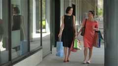Happy young women with shopping paperbags pointing finger at shop window in city Stock Footage