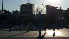 Silhouettes of children while playing street basketball at sunny summer day. Stock Footage
