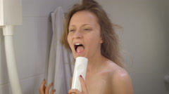 Young slim woman in bathroom of hotel singing in hairdryer and dancing , looking Stock Footage