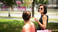 Beautiful smiling female friends with shopping bags in hands walking by street Stock Footage